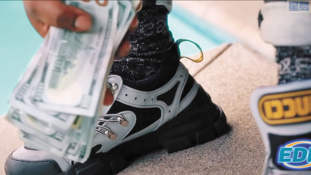 音樂片「EDD」的截圖,一人手持一疊百元美金。Nuke Bizzle/YouTube