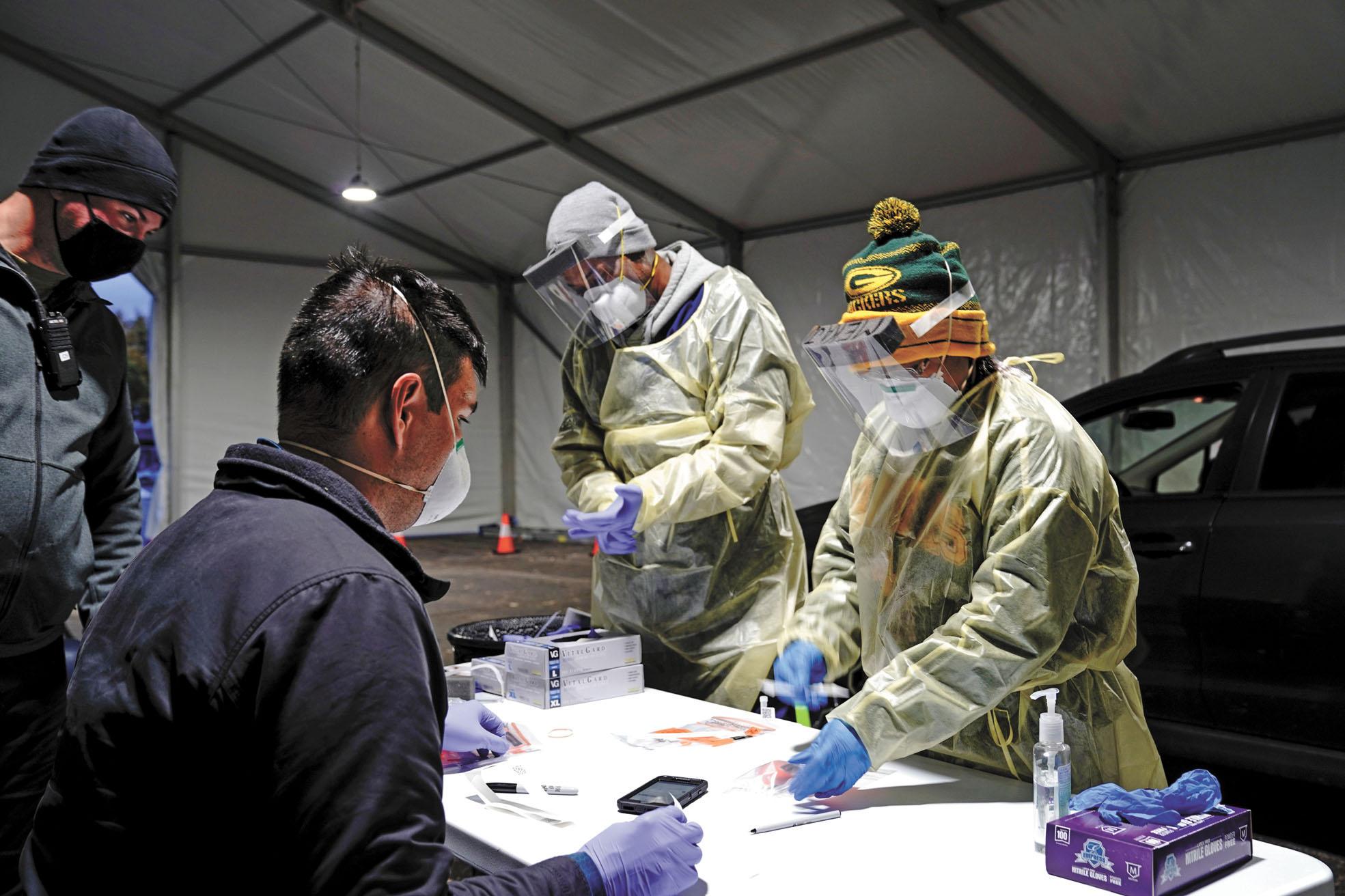 全美單日新增病例連續第二天接近8.4萬人,創下新冠疫情爆發以來的第二高紀錄。圖為工作人員正在進行核酸檢測。路透社