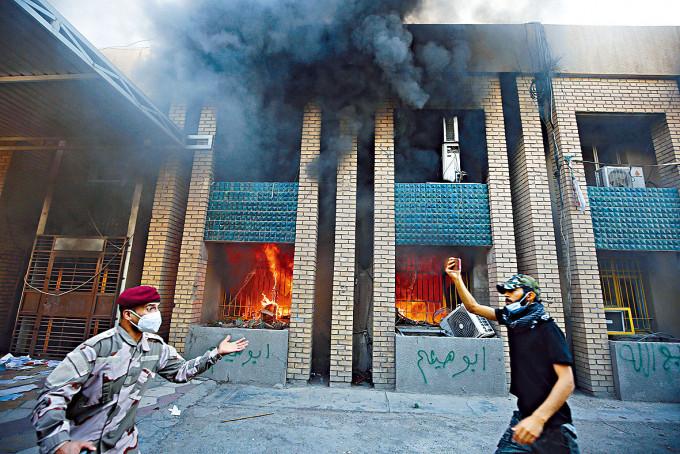 巴格達安全人員(左)上周六阻止親伊朗的伊拉克示威者,焚燒庫族政黨總部。