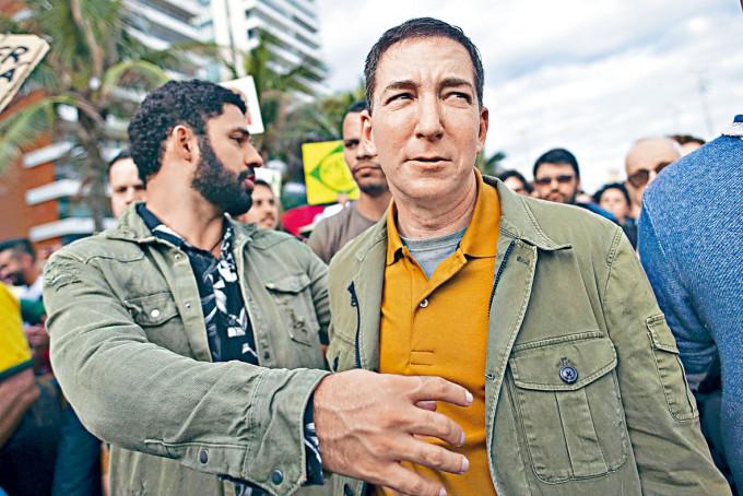 格林沃爾德(右)去年與巴西籍丈夫在里約熱內盧參加保護亞馬遜森林示威。