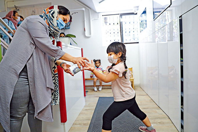 德黑蘭幼稚園學生回校時以搓手液消毒。