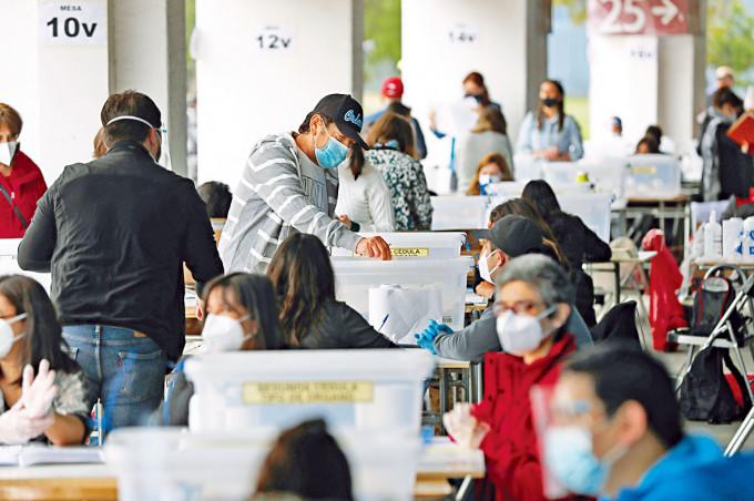 智利選民昨日把公投選票放進票箱。