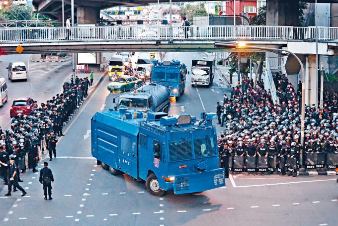 警方昨日出動的水炮車駛過曼谷街頭,道路兩旁有大批防暴警察。