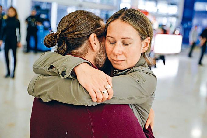 一名男子昨在雪梨機場擁抱由紐西蘭抵埗的伴侶。