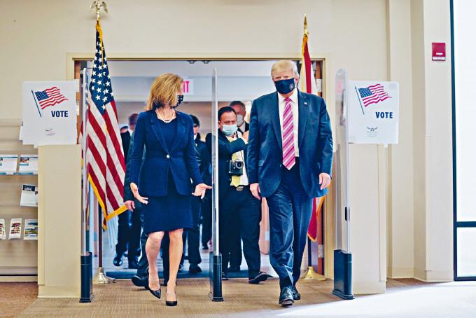 特朗普(右)昨到佛州西棕櫚灘票站投票後,由縣選舉監督員陪同離開。