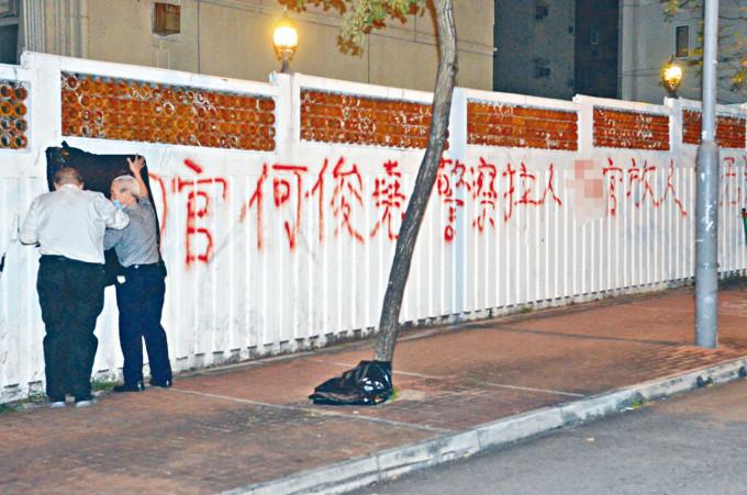 屋苑圍牆被人噴上辱罵法官字句,保安員用黑膠袋遮蔽。