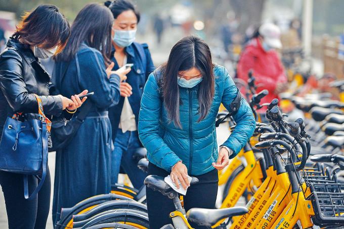 再傳疫情,北京民眾使用共享單車也小心清潔。