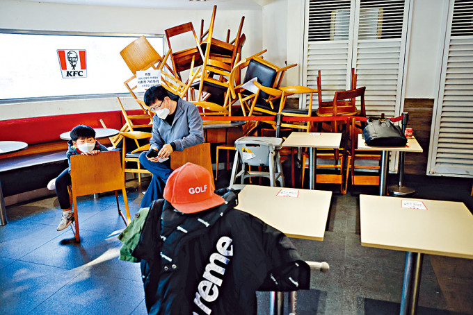 南韓果川市一對戴口罩父子在餐廳旁等候入座。