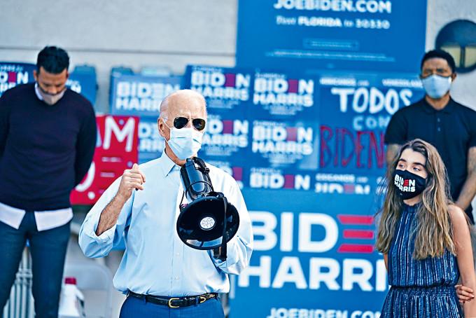 拜登在孫女(右)陪同下在佛州的集會向支持者講話。
