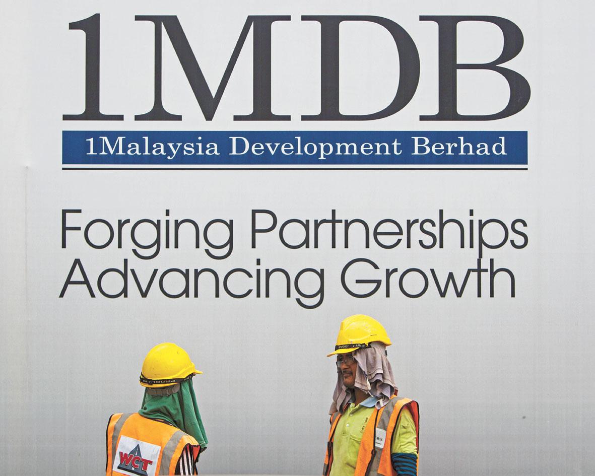 圖為建築工人在1MDB的廣告牌前聊天。美聯社