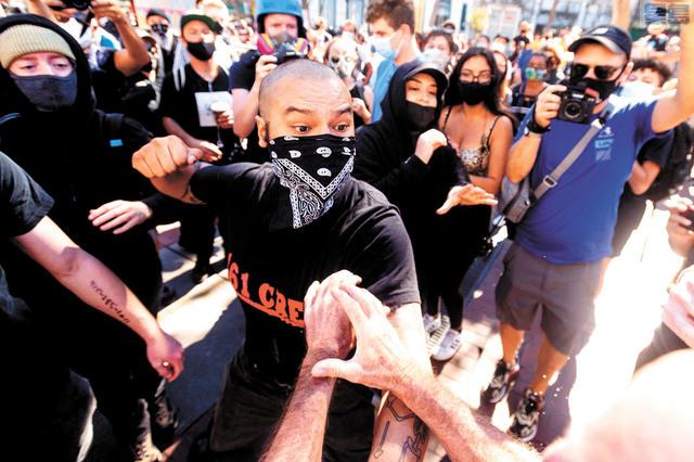 一名拒絕透露姓名的反法西斯蒙面示威者,握拳準備打保守派集會人士。美聯社