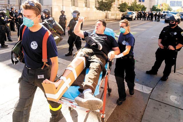 支持特朗普的男子遭攻擊,被送上救護車。美聯社