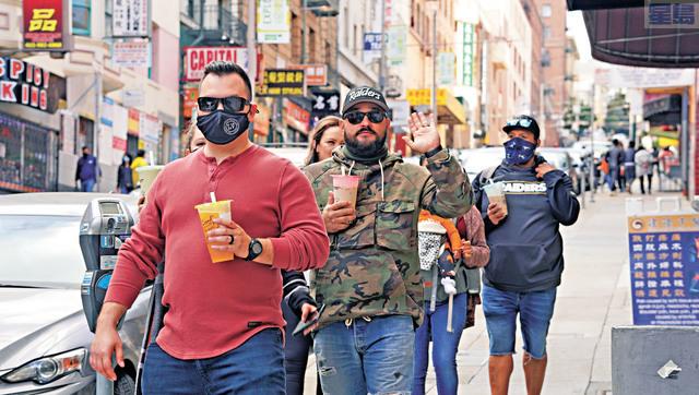 途經華埠的遊客,最常見的是人手一杯珍珠奶茶。記者黃偉江攝