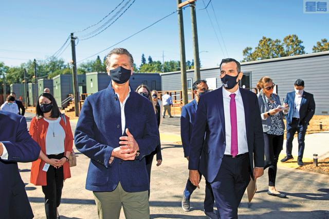 州長紐森(左)周五在聖荷西市長李卡多(右)等陪同下,到訪聖荷西Monterey路近日開放的組合屋。美聯社