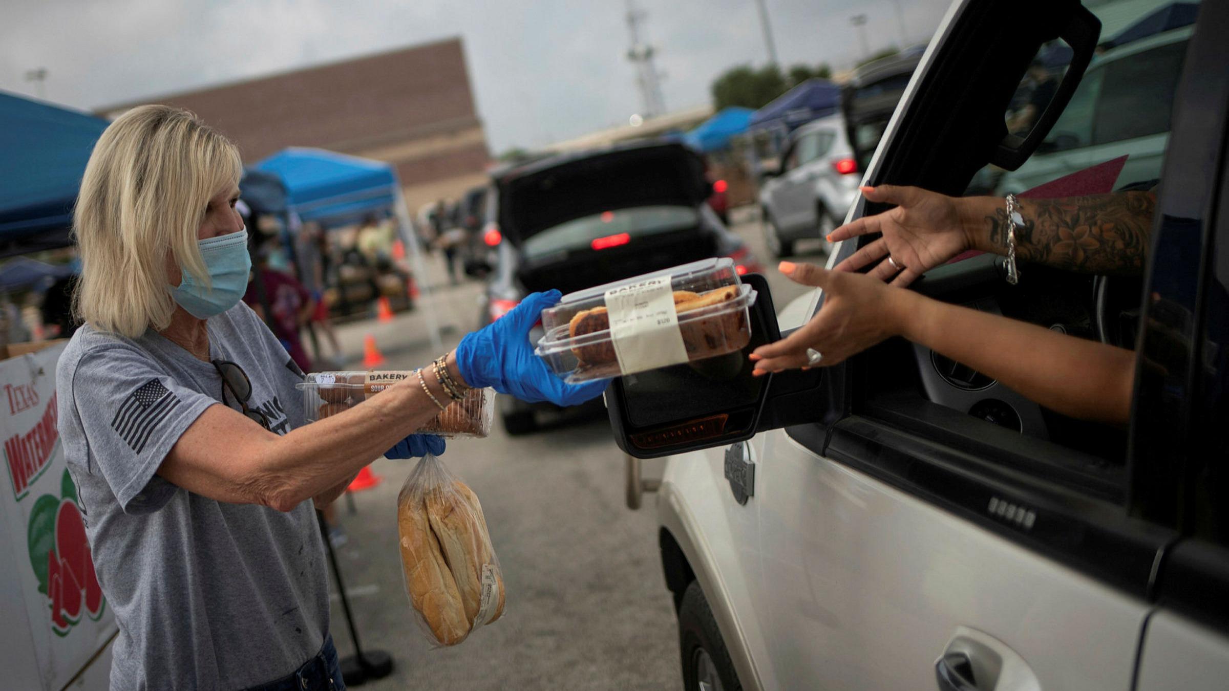 數據分析顯示,有愈來愈多民眾陷入飢餓,每8個人之中,就有1人吃不飽。圖為德州聖安東尼奧市一名義工,將麵包交給駕車居民。    路透社