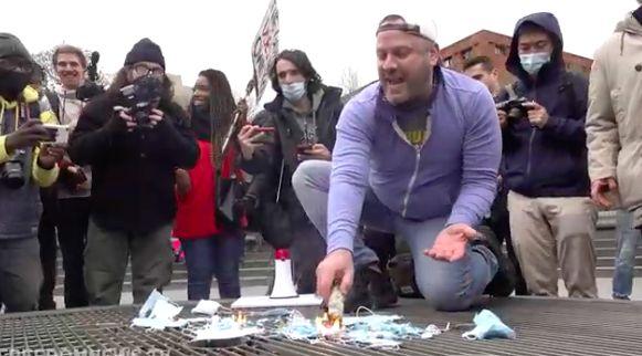 ■一名示威者在示威人群的圍繞歡呼下點燃 口罩。 Freedomnews.tv