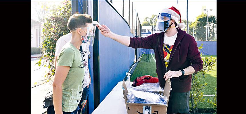 各州為防範感恩節後病毒傳播增加,都宣布加強民眾返家時的防控措施。圖為洛杉磯縣為其1000萬居民,實施居家令,有義工上門進行體溫測量。法新社