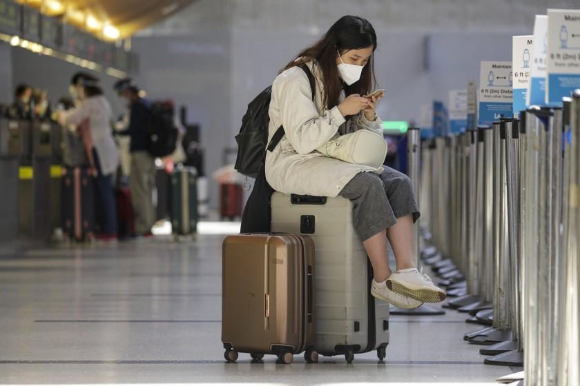 洛杉磯國際機場一名戴著口罩的旅客。洛杉磯時報
