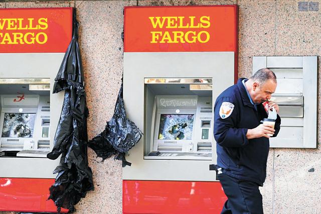一名私人保安人員手拿口罩經過洛市遭破壞銀行自動提款機。美聯社