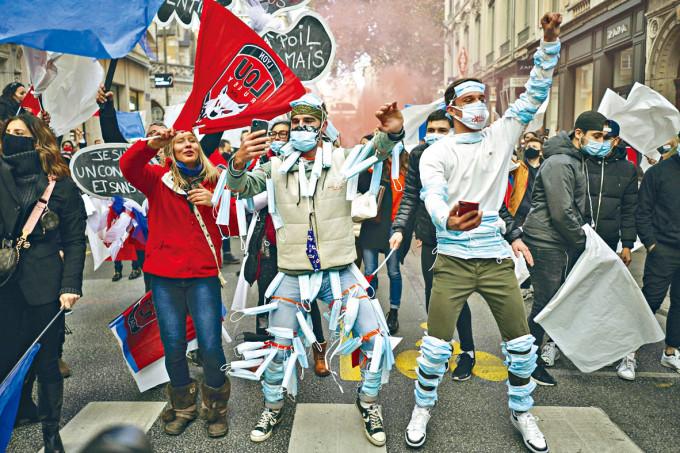 法國里昂周一有一批在身上穿戴口罩的示威者,抗議夜店、酒吧關閉。