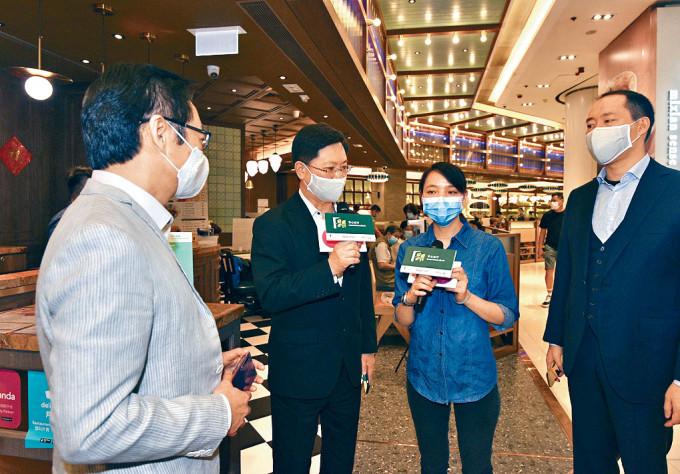 創科局局長薛永恒(左二)昨到荃灣區,聽取茶餐廳店長講述應用「安心出行」的好處。