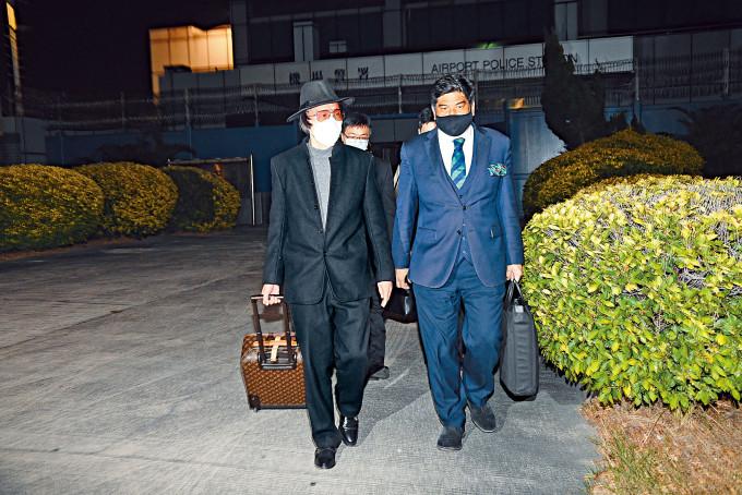戴上帽子及口罩的「上海仔」郭永鴻,昨晚拖着名牌行李篋,由律師陪同下離開機場警署。