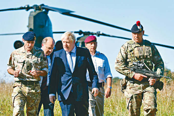 約翰遜去年到英格蘭索爾茲伯里平原訓練區探望軍人。