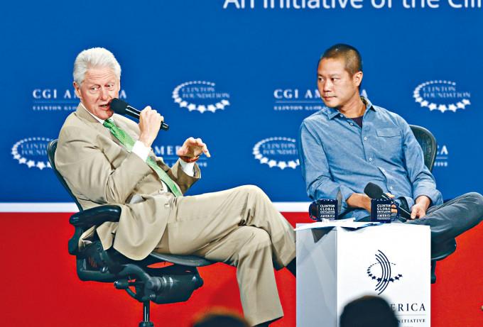 二○一四年謝家華(右)出席丹佛市一個論壇,與前總統克林頓對談。