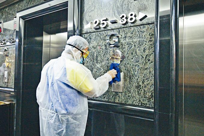 灣仔三湘大廈Starlight Dance Club出現小型爆疫,清潔員穿上防護衣在大堂進行消毒。