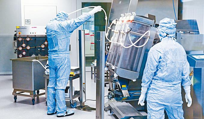 德國生物技術公司IDT Biologika人員操作製造疫苗機器。