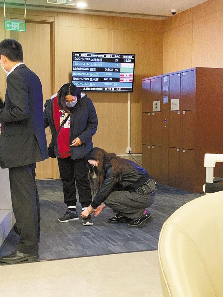 張萌蹲在地上幫懷有身孕的助理系鞋帶。 網上圖片