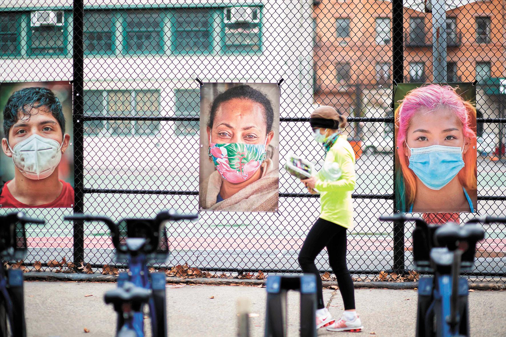 美國疫情日益嚴峻,戴口罩的民眾增多。圖為民眾路過「蒙面紐約」 攝影作品展覽。法新社