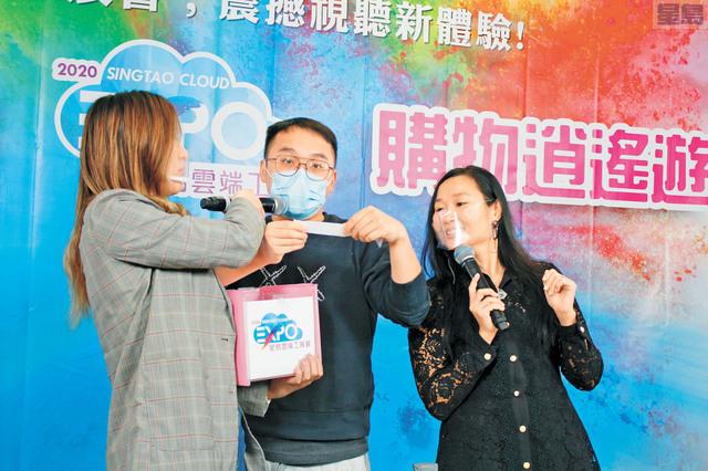 星島中文電台粵語台節目總監麥翔雄(中),為參與「指手畫腳」遊戲的觀眾,進行抽獎,送出禮物。本報記者張曼琳攝
