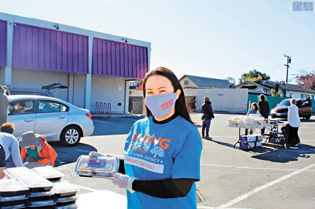 市議員盛濤在現場向市民發放食物和新鮮蔬菜。她戴著在本次活動中分發給居民的可重複使用的防護口罩。記者張曼琳攝