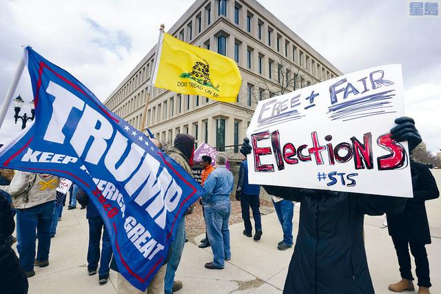■密歇根州的選舉官員23日宣布,確認民主黨人拜登以在該州的得票比特朗普多15.4萬的點票結果在該州勝選。圖為選舉委員會在開會時,有示威者在辦公樓外面抗議。    美聯社