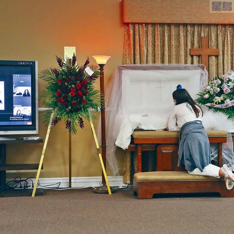 ■美國新型冠狀病毒累計1256萬宗確診個案,近26萬人死亡。圖為一名女孩在死於新冠病毒的父親葬禮上。送葬的親友則在網上出席視像葬禮。    法新社