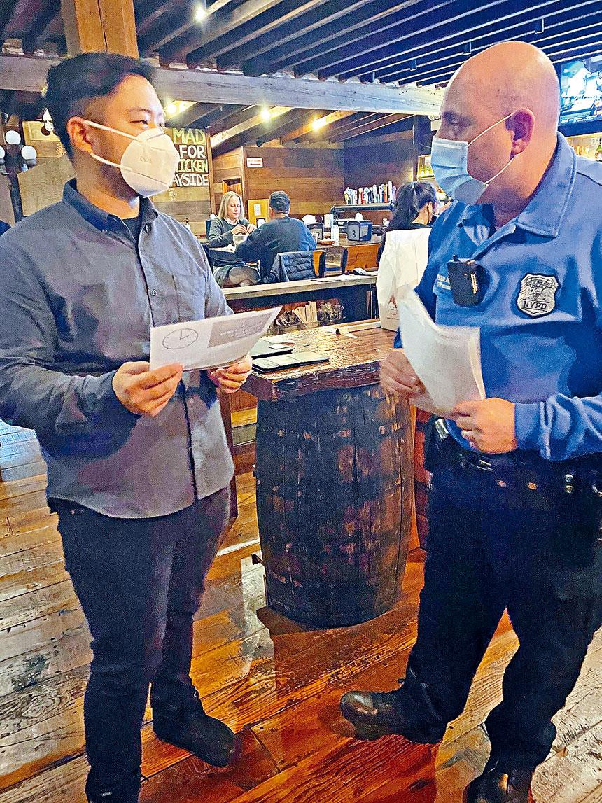 111分局警員在貝賽商業區餐廳與酒吧業者派發限制營業時間及防疫措施的傳單。