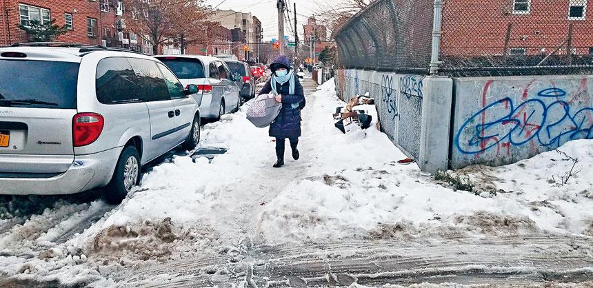 法拉盛市中心的街道無人鏟雪,行人步履維艱。黃敏儀提供
