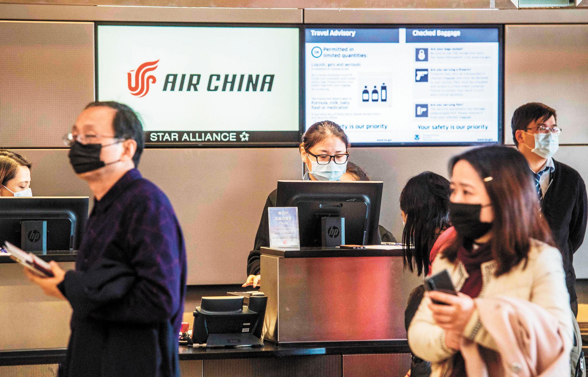 美國針對中國接連做出簽證限制,受此限制影響的中方人員規模尚不清楚。圖為在洛杉磯國際機場,戴著口罩的中國公民在辦理飛北京的登機手續。法新社資料圖片
