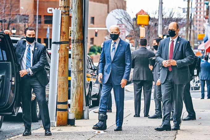 日前扭傷腳的拜登周二介紹經濟團隊後,可見他右腳穿保護靴離開會場。