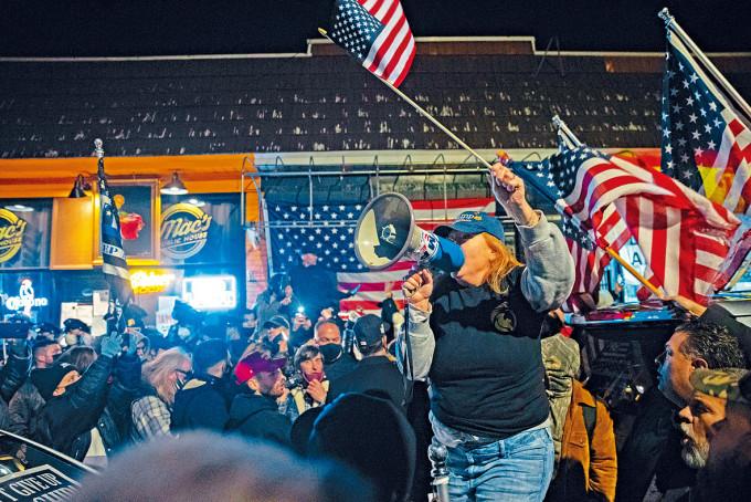 紐約州一間酒吧因拒遵從防疫限制而被勒令關閉後,有民眾在酒吧外抗議。