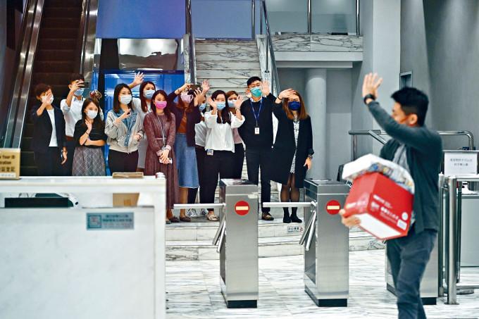 有收到解僱通知的員工,離開公司前與同事揮手道別。