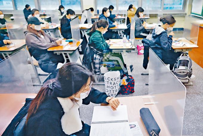 首爾一個高考試場的考生昨天參加考試,桌上設有隔板。