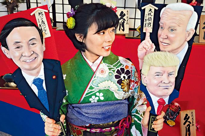 東京有玩具公司僱員展示印有拜登、特朗普和菅義偉肖像的板羽球木拍。