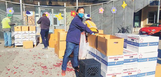 邱信福幫忙包裝食物。他每星期都會定時前往食物銀行的派發點幫忙。記者李兆庭攝