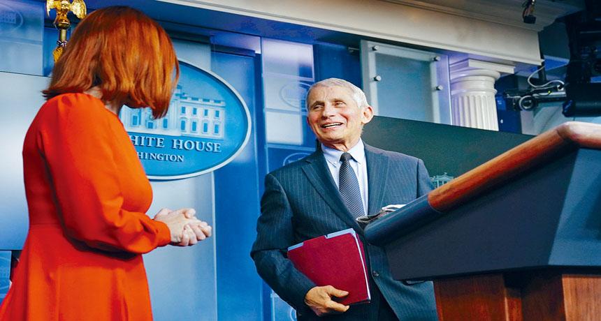 國家過敏和傳染病研究所所長福西在白宮發言人普薩基(左)陪同下,在白宮記者會上回答記者的抗疫策略問題。     美聯社