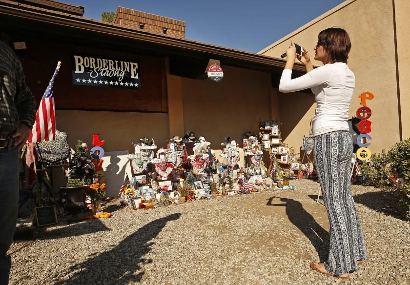 千橡樹市於2018年發生大規模槍擊案件的酒吧門前放滿了十字架與花束。洛杉磯時報