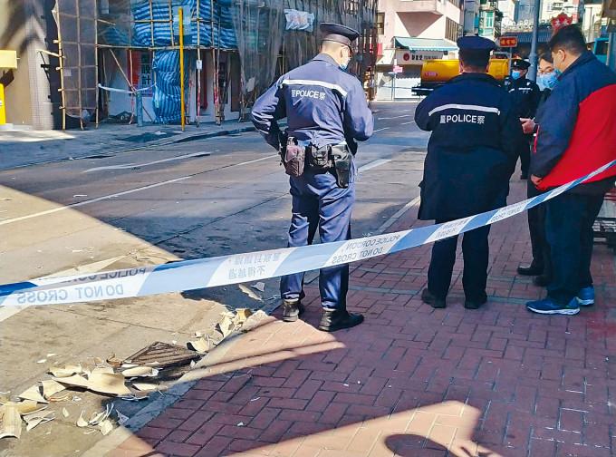 大廈外牆雨水管甩脫墮街,碎片滿地,警方封路以策安全。
