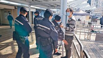 藍帽子警員截查一名中大學生。
