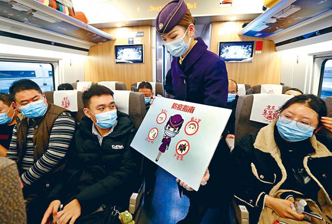 春運在即列車員向乘客講解防疫指南。